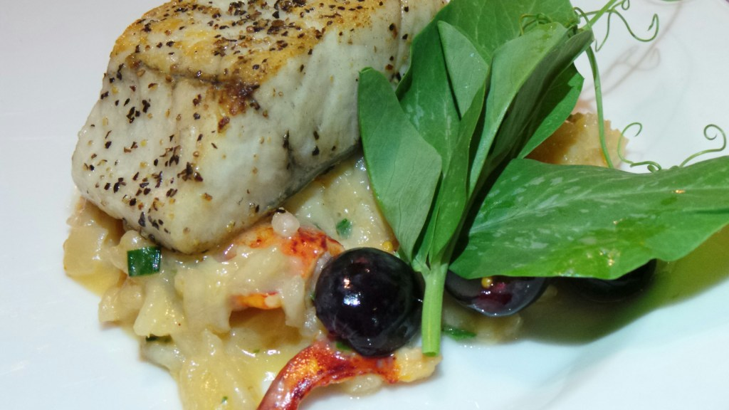 Pan-seared barramundi with lobster risotto, pickled black grapes and pea tendrils