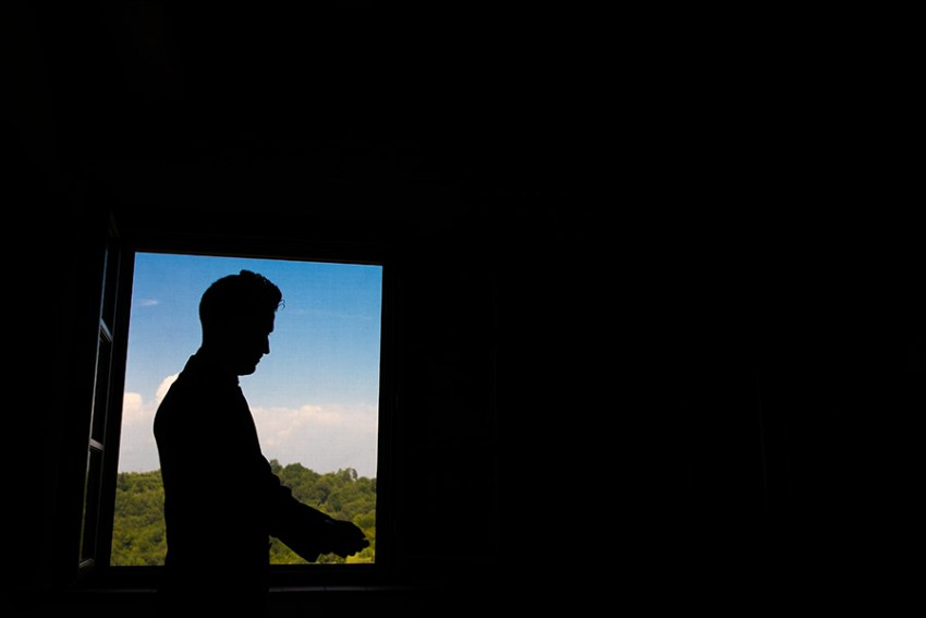 Silhouette of groom getting ready