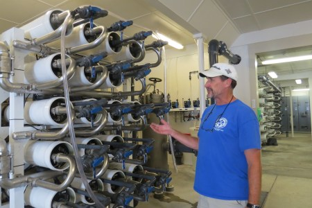 Water plant manager Dave Tolson explains how the salty water is pushed through these membranes to filter the salt. Photo by C. Leinbach