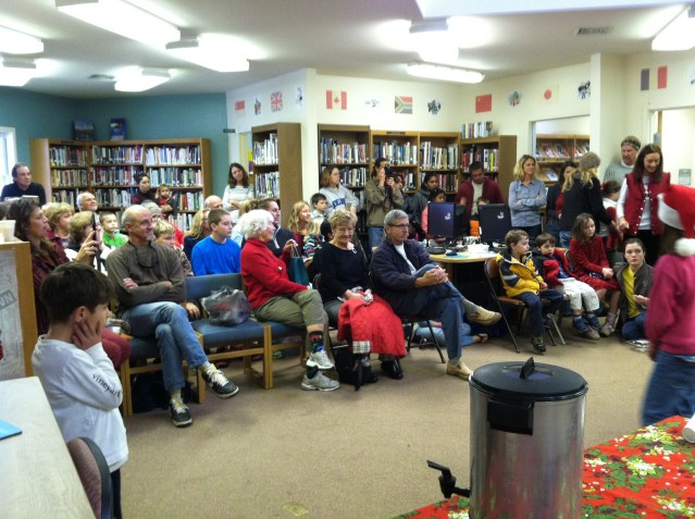 At the Cookie Swap in the Ocracoke Community Library, school children sing holiday songs. This year's Cookie Swap is Sunday, Dec. 6 at 11 a.m. Note change of date.