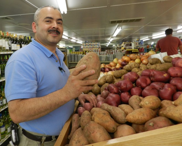 Mauro Ibarra show a sweet potato in the Ocracoke Variety Store.