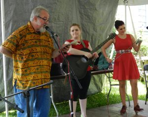 Bob Zentz, left, introduces Maggie and Cassie MacDonald at the workshop stage of the Ocrafolk FEstival.