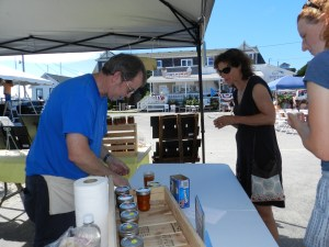 John Simpson, left, gives out samples of Trudy Austins fig-peach preserves Friday during the Ocracoke Fig Festival.