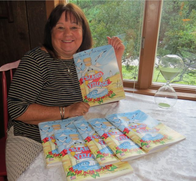 Mary Vankevich with her 'Island Village' coloring book featuring images of Ocracoke. Photo: C. Leinbach