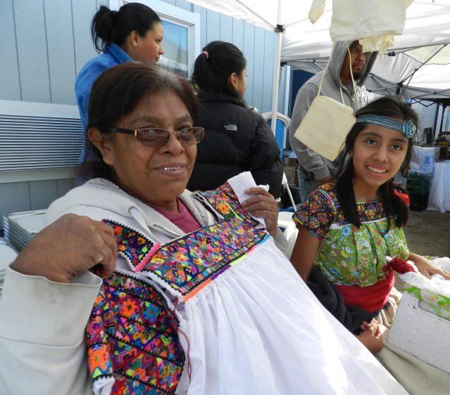 Laja Candelaria, a la izquierda, exhibe su obra: decoración a mano, una camisa con el estilo de la región de Puebla de México.decoration for a shirt in the style of the Puebla region of Mexico.