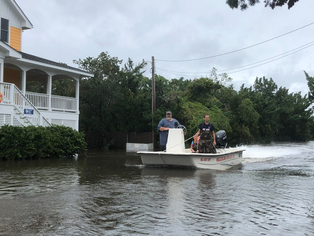 a boat moves down a road flooded by Hurricane Dorian
