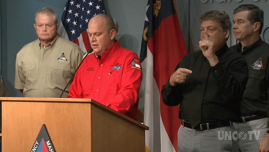 A man stands at a podium talking about Hurricane Dorian