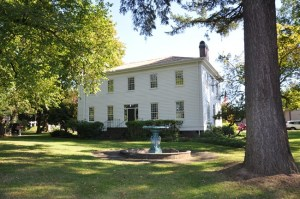 exterior of two story frame house with trees and fountain