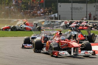 © Octane Photographic Ltd. 2011. Formula 1 World Championship – Italy – Monza – 11th September 2011  Viantonio Liutzi (HRT) arrives sideways on the grass leading to a huge collision as Fernando Alonso (Ferrari) and Sebastian Vettel (Red Bull) lead the pack on lap 1 – Race – Digital Ref :  0177CB7D7843