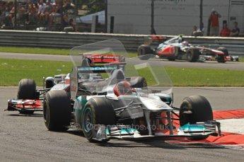 © Octane Photographic Ltd. 2011. Formula 1 World Championship – Italy – Monza – 11th September 2011 Michael Schumacher bounces his Mercedes onto 3 wheels under pressure from Lewis Hamilton's McLaren – Race – Digital Ref : 0177CB7D8081