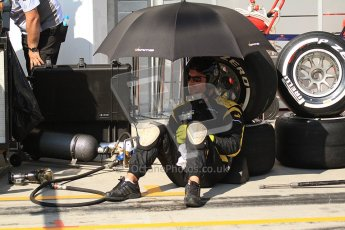 © 2012 Octane Photographic Ltd. Hungarian GP Hungaroring - Saturday 28th July 2012 - Lotus GP mechanic sheltering from the blistering sun. Digital Ref : 0431cb7d0701