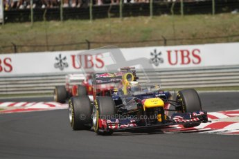 © 2012 Octane Photographic Ltd. Hungarian GP Hungaroring - Sunday 29th July 2012 - F1 Race. Red Bull RB8 - Sebastian Vettel bounces high over the curbing whilst being chased by the Ferrari F2012 of Fernando Alonso. Digital Ref :