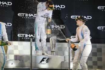 World © Octane Photographic Ltd. Sunday 23rd November 2014. Abu Dhabi Grand Prix - Yas Marina Circuit - Formula 1 Podium. Mercedes AMG Petronas – Lewis Hamilton - Race winner and 2014 World Champion and Williams Racing - Valtteri Bottas (3rd). Digital Ref: 1173CB1D1132
