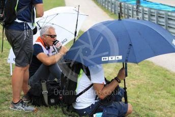 World © Octane Photographic Ltd. Formula 1 – Hungarian GP - Practice 2. RTL video/commentary team sheltering under umbrellas. Hungaroring, Budapest, Hungary. Friday 2nd August 2019.
