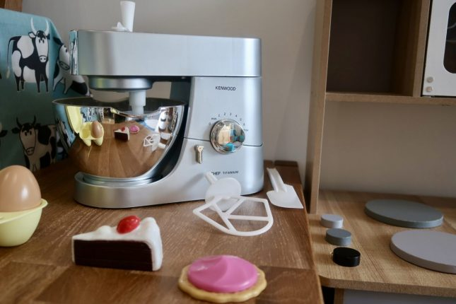 A Kenwood Toy Mixer on a wooden table, next to a wooden kitchen and with plastic cakes and eggs in front of it