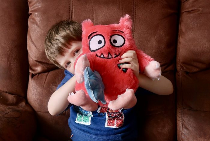 A boy holding out a fluffy Love Monster toy and peeking out from behind it