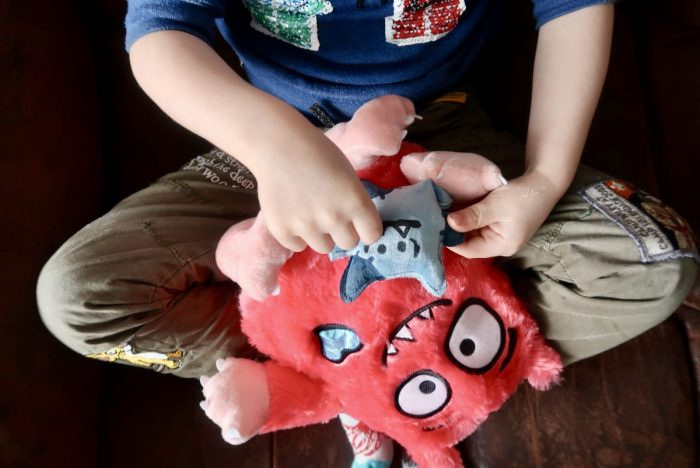 A boy playing with a Love Monster toy on his lap
