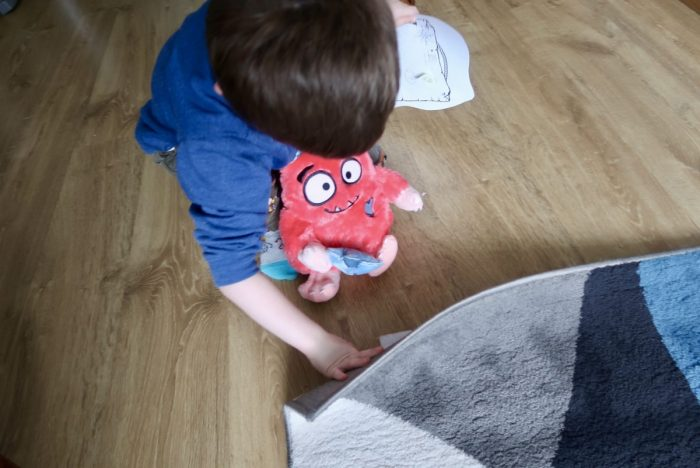 A little boy looking under a rug and holding a Love Monster stuffed toy