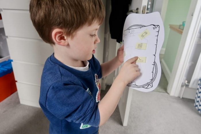 A boy pointing at pictures on a treasure map