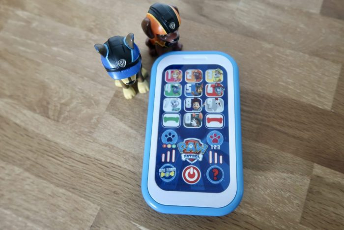 A Paw Patrol Smart Phone toy with 2 plastic pups next to it