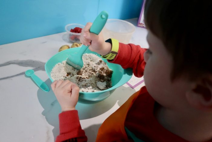 A child stirring a green mixing bowl