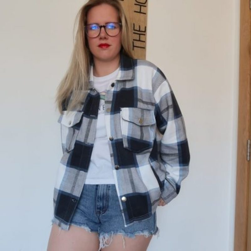 A girl wearing denim shorts and a grey and white checked shacket