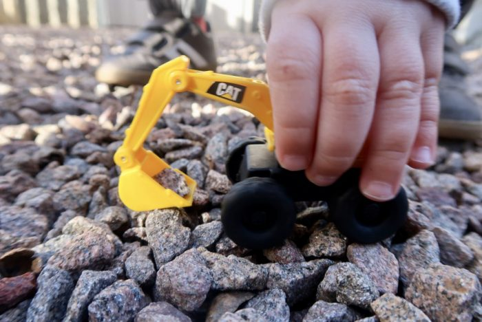 A childs hand holding a toy digger