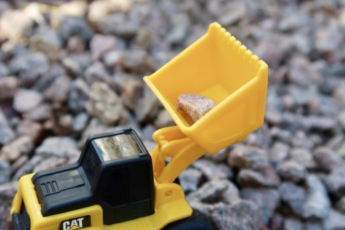 A toy construction vehicle with a stone in the lifter
