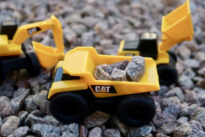 A toy dump truck with little stones in it