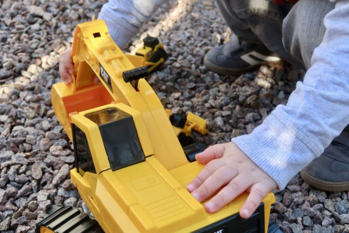 A Cat digger with a childs hands on it