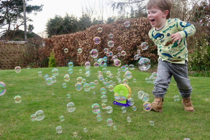 A little boy running through bubbles coming out of a bubble machine