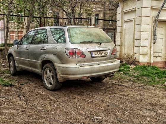 автомобиль припаркованный на уничтоженной траве в парке Шевченко