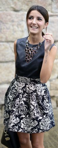 Black floral skirt, leather top in combination with stylish necklace create universal elegant look.