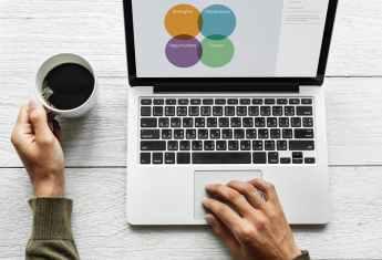 person using macbook pro while holding ceramic mug on gray wood surface