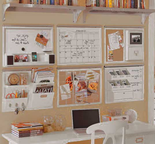 удобный рабочий стол ребенка с стендами и книжками на стене