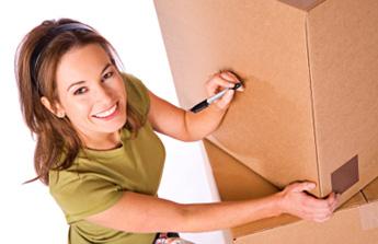 девушка подписывает коробки с имуществом