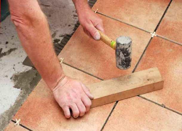 Удары по плитке резиновым молотком через брусок