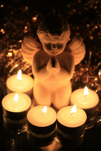 A praying angel surrounded by burning votive lights