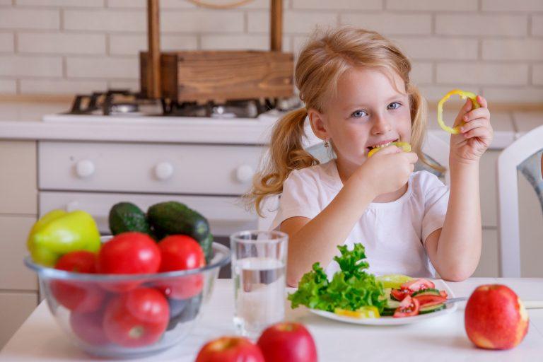 Dziewczynka siedzi przy stole w kuchni i je warzywa