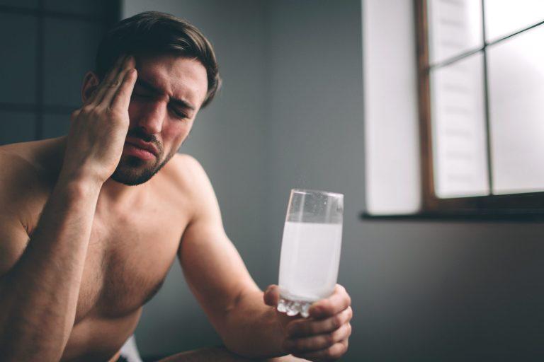 Jak pozbyć się kaca? Mężczyzna na kacu trzyma w ręku szklankę z musującą aspiryną