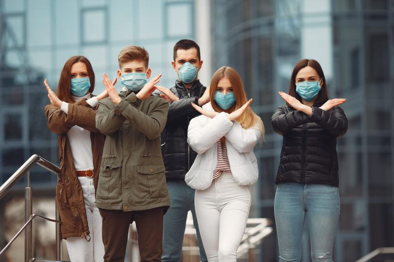 Grupa młodych ludzi w maseczkach ochronnych