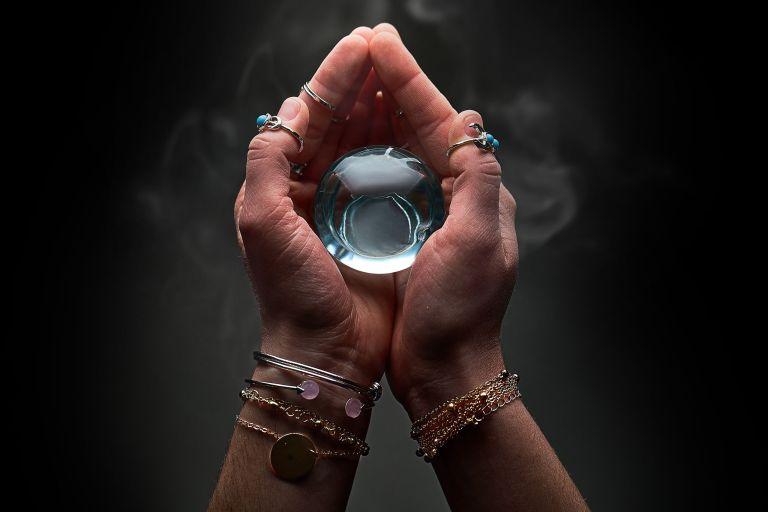 Jasnowidz trzyma w dłoniach szklana kulę. W czasach niepewności zwracamy się w stronę wróżb.