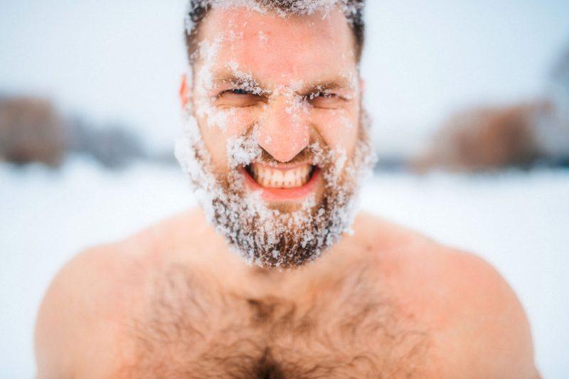 Zbliżenie na meżczyznę, który morsuje na sniegu bez ubrania. Jego twarz i broda pokryte są kryształkami lodu.
