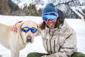 Mężczyzna w goglach z psem w okularach przeciwsłonecznych, na tle zimowego krajobrazu