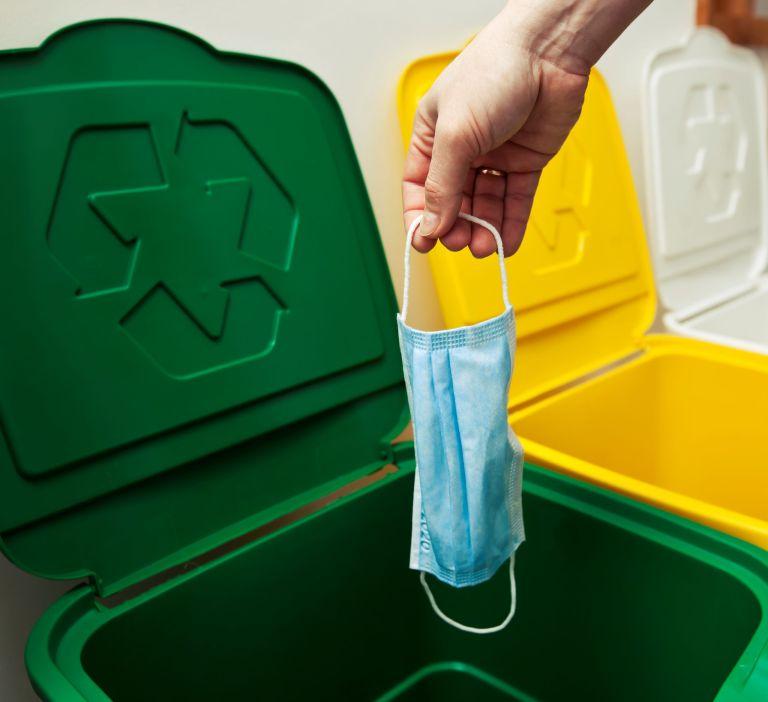 Kobieta wyrzuca zużytą maseczkę do zielonego kosza z odpadami do recyklingu