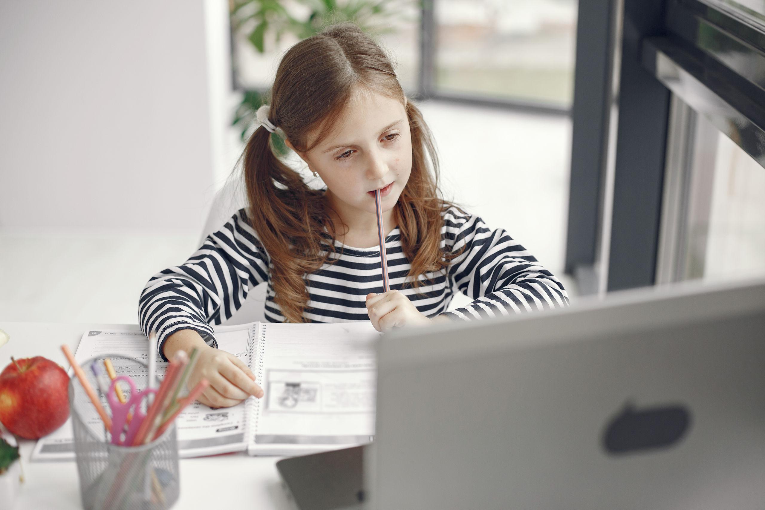 Dziewczynka w skupieniu odrabia lekcje na laptopie