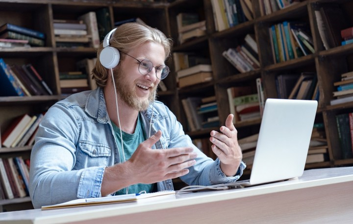 Young male teacher with headphones on at desk with computer. Bookshelf in the background