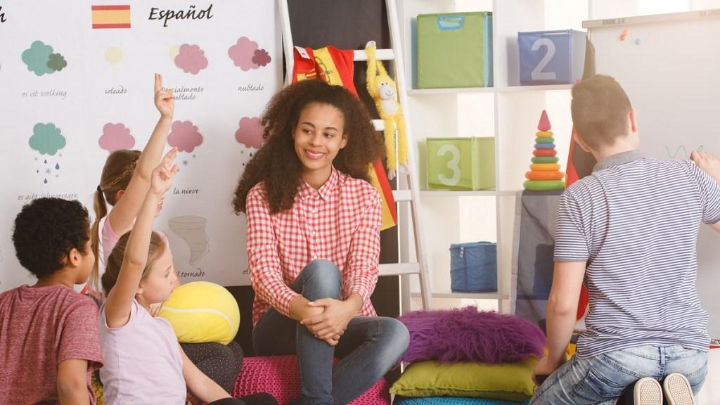 Teacher in classroom teaching foreign language (Spanish) to children sitting on floor