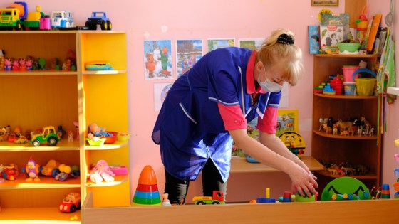 Child care worker wearing face mask tidying up toys in play room