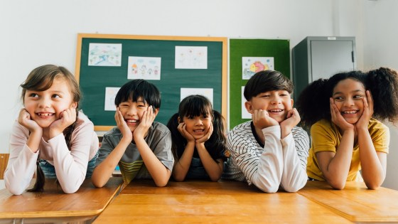 Diverse school children smiling as they lean over their desks in the classroom